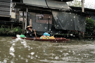 A woman makes her way to the floating market of Damnoen Saduak, Thailand