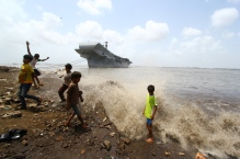 Children play in front of the historic INS Vikrant, India's first aircraft carrier dismantled in 2014.